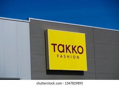 TOENISVORST, GERMANY - MARCH 22. 2019: Yellow logo of Takko fashion(German fashion chain) on a facade against clear blue sky