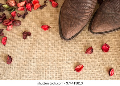 toes of cowboy boots on country fabric with dried red flowers all around - negative space on bottom left