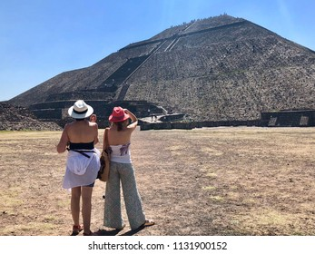 TOETIHUACAN, MEXICO - May 28, 2018: Two young female tourist look at the Pyramid of the Sun in Teotihuacan before climbing it.