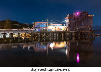 Tofino, British Columbia, Canada September 19, 2019 - Beautiful water reflection at night of the historic & popular water front Ice House Oyster Bar located on a pier at the end of Main Street.