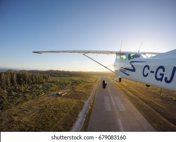 Tofino, Vancouver Island, British Columbia, Canada - June 29, 2017 - Small Cessna 172 Airplane taking off from the airport runway during a bright sunny sunset.