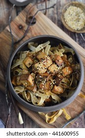 Tofu Stir Fry with Sesame Seeds and Sesame Noodles in a Brown Bowl