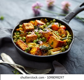 Tofu with vegetables sprinkled with herbs and edible flowers. Vegan dish delicious and nutritious. Healthy eating concept