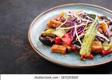 Tofu with vegetables. stir fry vegetables with pieces of tofu, coriander, cumin, cream and butter with a little soy sauce and oyster sauce - served with jasmine rice. Appetizing dish, served on a plat