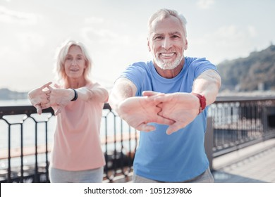 Together is better. Senior pleasant unshaken man standing with a woman smiling and training on the quay.