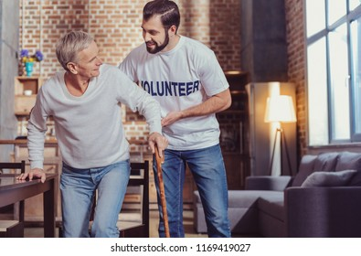 Together easier. Attentive careful responsible man standing near a senior man smiling and supporting a retired.