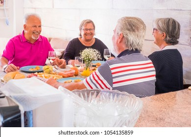 together firends having lunch at home. aged men and women drinking wine durgina home party. friends concept forever