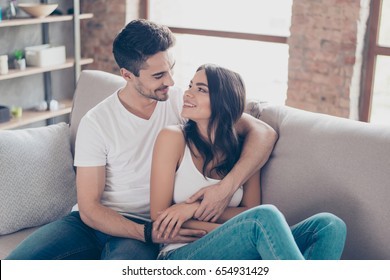 Together forever. A couple of young beautiful lovers are cuddling indoors on the couch and looking deep into eyes of each other with love