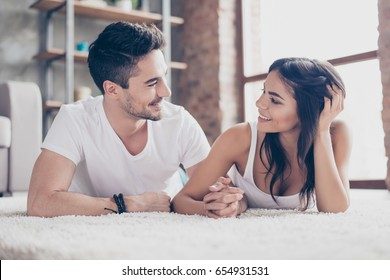 Together forever. A couple of young beautiful lovers are lying on the beige cozy carpet indoors at home, holding hands and looking deep into eyes of each other with love and tenderness
