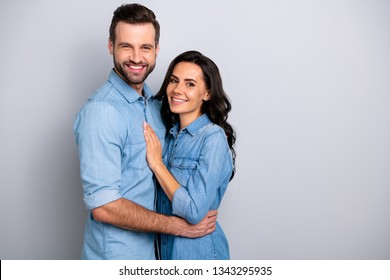 Together forever. Portrait of handsome charming married people spouses isolated feeling cheerful joyful wearing denim shirts on silver background
