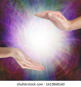 Together our healing energies combine to create a powerful influence - male hand opposite female hand with a white light orb in between against a multicoloured flowing energy field background with cop
