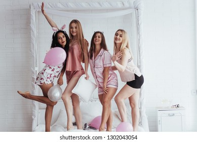 Together this day. Standing on the luxury white bad at holiday time with balloons and bunny ears. Four beautiful girls in night wear have party.
