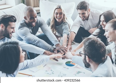 Together we are stronger! Group of happy business people holding hands together while sitting around the desk