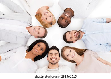 Together we are stronger. Top view of cheerful group of multi-ethnic people laying on their backs and smiling while standing isolated on white