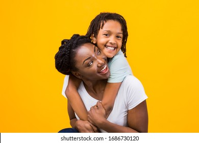 Togetherness Concept. African daughter hugging her mum from the back, showing her love, yellow studio wall