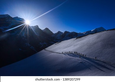Togetherness concept: Silhouette a group of hikers with sun at the background during an expedition to Thorong-la Pass via Annapurna Circuit