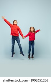 Togetherness. Happy children isolated on blue studio background. Look happy, cheerful. Copyspace for ad. Childhood, education, emotions, facial expression concept. Jumping high, flying smiling