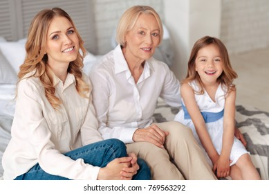 Togetherness and unity. Delighted nice positive family sitting together on the bed and looking at you while feeling happy together