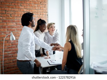 togetherness at work. cheerful office people putting joining their hands while standing nera the panorama window in the loft room