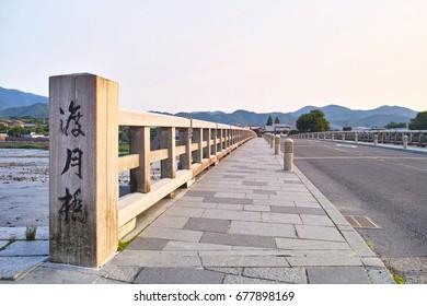 "Togetsu bridge crossing the Katsuragawa early morning in Kyoto Arashiyama. On the left side of the photo is the Japanese kanji name of ""Togetsu Bridge"" engraved."