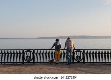 Togliatti, Russia - 9 May 2019: Old couple with dog enjoying scenery view at river Volga embankment