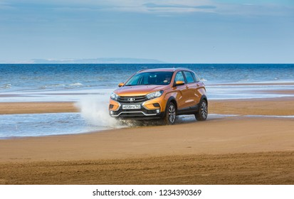 TOGLIATTI, SAMARA / RUSSIA - SEPTEMBER 13, 2018: LADA XRAY Cross. Presentation the new vehicle production of AVTOVAZ. Off-road car on the bank of VOLGA-river with sand, water, and roadless conditions