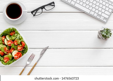 to-go box with salad, coffee for lunch in office and keyboard on white wooden background top view mockup