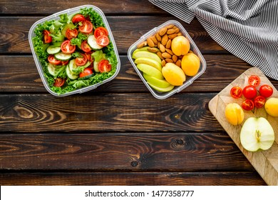 to-go box with salad and fruit for lunch on wooden background top view copyspace