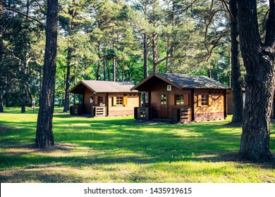 TOILA, ESTONIA - June 04, 2019: Wooden bungalow row in camping camp park in forest. Vacation houses in camp's park. Adventure, travel, summer holidays concept.