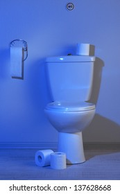 Toilet bowl and toilet paper in a bathroom with blue light