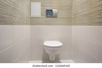 Toilet design with built-in toilet. Built-in toilet is made as an installation, all the elements, except for the toilet are hidden behind the tiles in the wall.