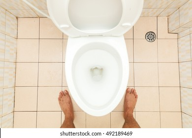 Toilet lavatory with bare feet standing,Dirty toilet, top view