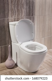 toilet with the lid open and accessories and brown bathroom tiles