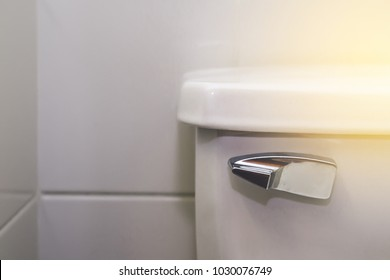 Toilet metal wc valve handle isolated on gray stone cement wall in bathroom . Faucet copy paste screen background