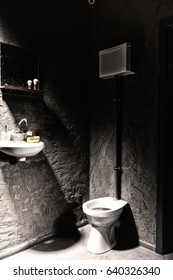 Toilet near washbasin with a soap box and toothbrush on it under the mirror with shave brush on the shelf in a dark prison cell