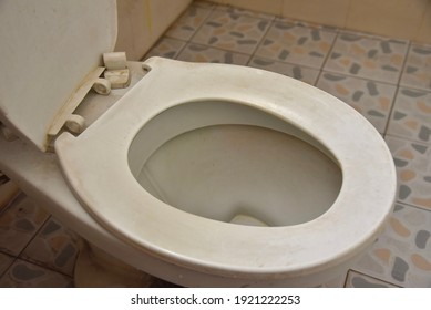 The toilet is old and dirty  With toilet lid components  The seats are broken and damaged.