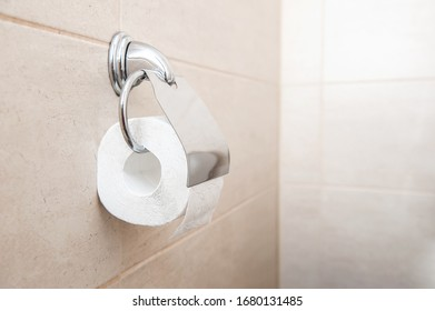 toilet paper hanging on a toilet paper holder. whole large roll, stocks, stock