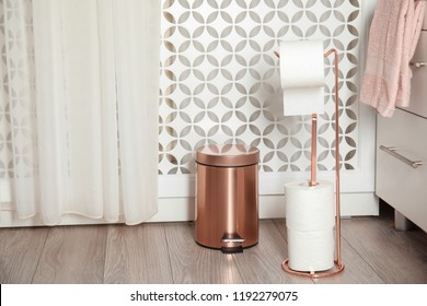 Toilet paper holder with rolls and trash bin in bathroom interior