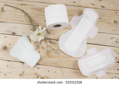 Toilet paper roll with white and dry flower, sanitary napkin and sanitary pads on the wooden table