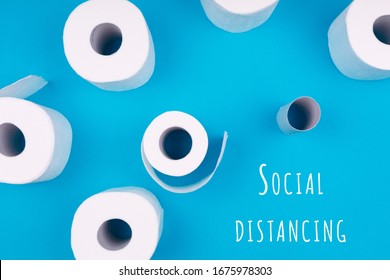 Toilet paper rolls on the bright blue background with Social distancing wording. Coronavirus pandemic panic shopping concept. Bright monochrome drop