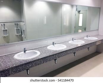 Toilet public men bathroom empty interior with sinks for washing hand mirror, urinals in clean restroom.