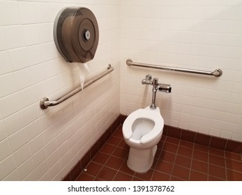 toilet and red square floor tiles in bathroom or restroom