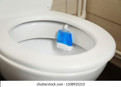 Toilet with rim block in bathroom. Air freshener