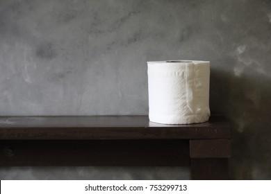 toilet rolled tissue on a wooden table in a restroom