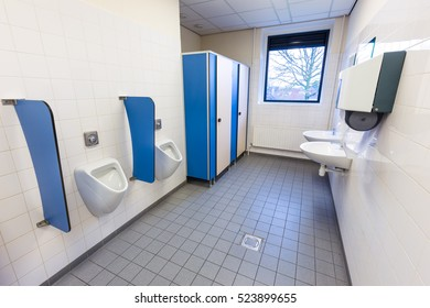 Toilet room for men with urinals sinks and towel dispenser on high school