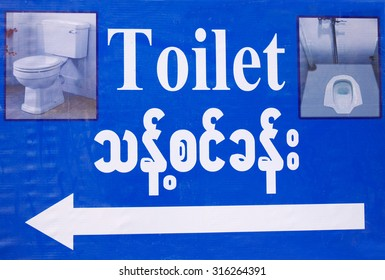 Toilet sign in English and Myanmar languages, with two types of example lavatories pictures and pointing arrow; on blue background.
