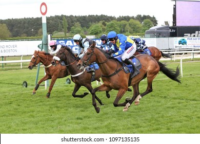 Tokay Dokey ridden by Harry Skelton (nearest) wins a thrilling four horse finish in the NH Flat Race at Market Rasen Races : Market Rasen Racecourse, Lincs, UK : 11 May 2018 : Pic Mick Atkins