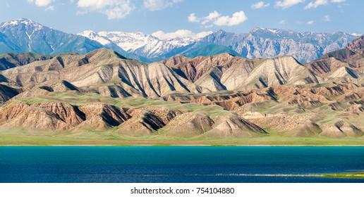 Toktogul lake under barren mountain range, Tien Shan range, Kyrgyzstan, Central Asia