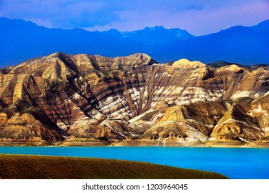 Toktogul, Tien Shan range, Kyrgyzstan, Central Azia. Beautiful scenic view, bright blue lake water under barren mountain range settled by the last sun rays at the background of dark evening sky