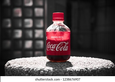 Tokyo, Akihabara/Japan - June 07, 2018: small coca cola bottle on a stone pillar with highlighting of the red color of the bottle